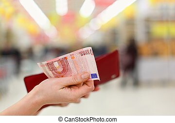 Woman hands gets money from her red purse in store; shallow depth of field