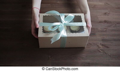 Woman hands giving gifts. Present made of recycled carton and  ribbon