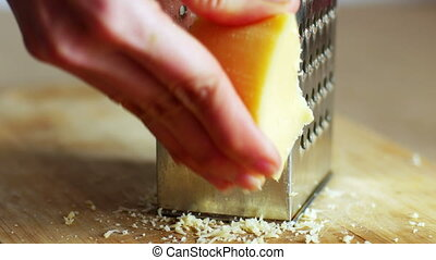 Woman hands grating yellow cheese with a grater, 4k close up