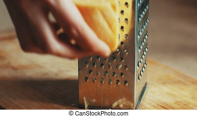 Woman hands grating yellow cheese with a metal grater, 4k close up. Graded