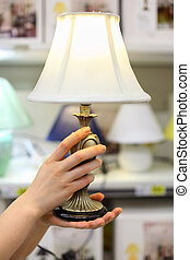 Woman hands hold beautiful table lamp in shop; shallow depth of field; focus on hands