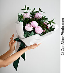 Woman hands hold bouquet of pink peony flowers on grey