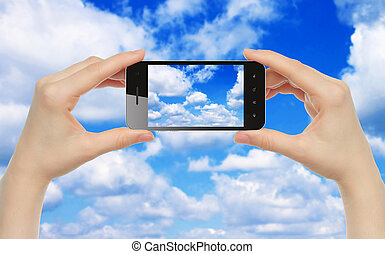 Woman hands hold smart phone with sky