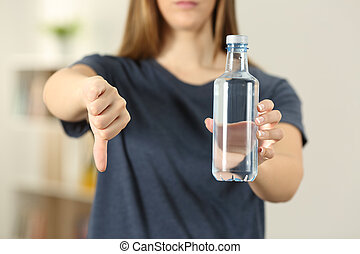 Woman hands holding a bottle of water with thumbs down