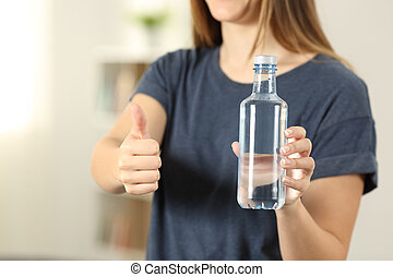 Woman hands holding a bottle of water with thumbs up