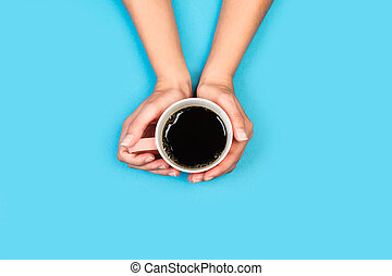 Woman hands holding a cup of black coffee on a light blue background