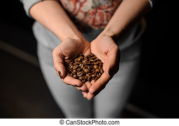 Woman hands holding a handful of fresh coffee beans