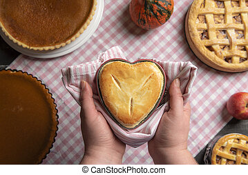 Woman hands holding a heart shaped pie above a table full of pies. Above view.
