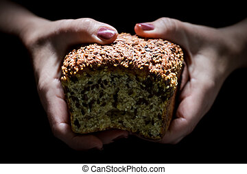 Woman hands holding a loaf of bread on black background