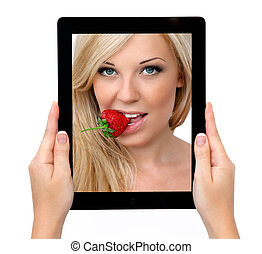 woman hands holding a tablet touch computer gadget with a beautiful sexy blonde with strawberry on the screen