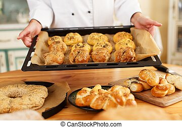 Woman hands holding baking tray with homemade baked goods