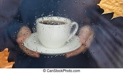 Woman hands holding cup of coffee through window with raindrops