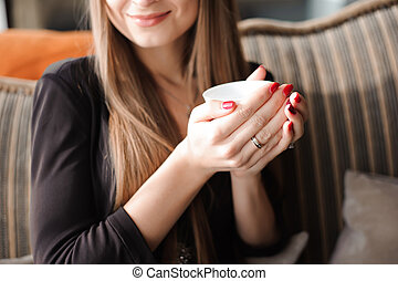 woman hands holding cup of hot drink