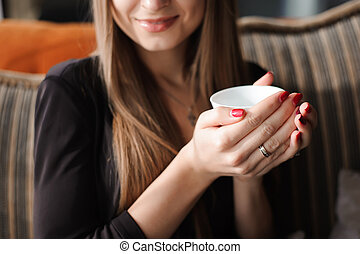 woman hands holding cup of hot drink.