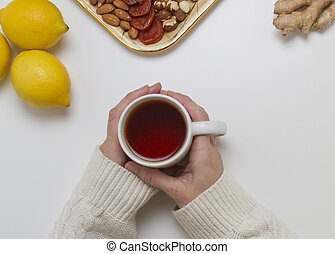 Woman hands holding cup of tea. Top view
