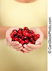 Woman hands holding fresh red cranberries closeup