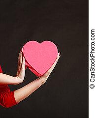 Woman hands holding heart box.