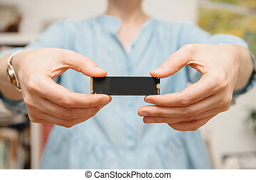Woman hands holding new NVME PCIE SSD hard drive disk with...