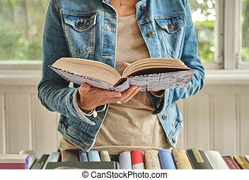 Woman hands holding open book in bookshop
