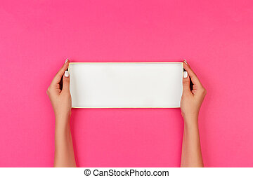 Woman hands holding open empty box on pink background, top view at the studio