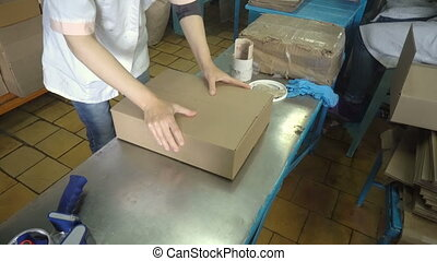 Woman hands holding packing machine and sealing cardboard...