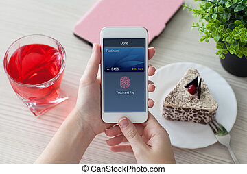 woman hands holding phone with debit card touch and pay