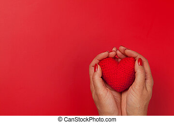 Woman hands holding red heart toy
