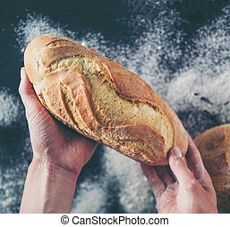 Woman hands holding tasty fresh bread, top view.
