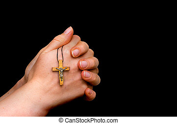 Woman hands holding wooden cross isolated on black