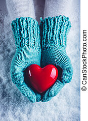 Woman hands in light teal knitted mittens are holding a beautiful glossy red heart in a snow background. St. Valentine concept.