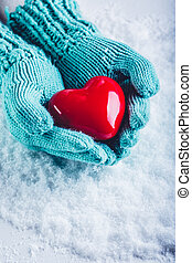 Woman hands in light teal knitted mittens are holding a ...