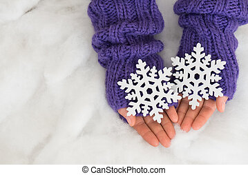 Woman hands in light teal knitted mittens are holding snowflakes on snow  background.