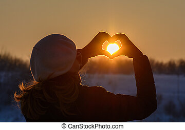 Woman hands in winter gloves. Heart symbol shaped, lifestyle and feelings concept with sunset light nature on background.