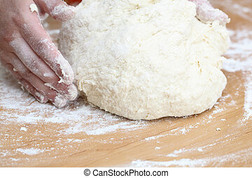 Woman hands knead the dough