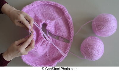 Woman hands knitting pink yarn
