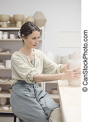 Woman hands makes clay pot on the pottery wheel