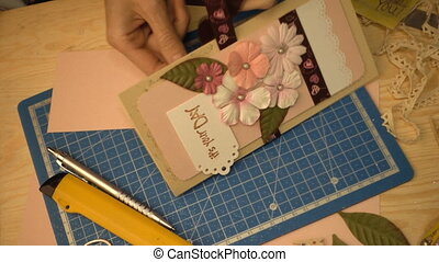 woman hands making a scrapbooking holiday gift postcard