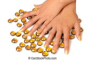 Woman hands manicure with gold nail polish on white background