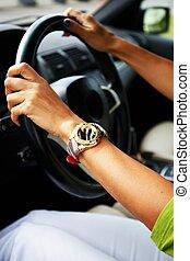 Woman hands on a steering wheel