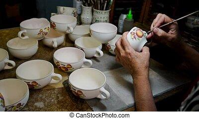 Woman hands paint earthenware figure - Close up female hands...