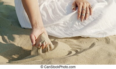 Woman hands playing with sand at beach. Beautiful scene of young boho gypsy girl with rings touching grit. Slow motion. High quality 4k footage