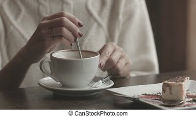 woman hands pouring sugar to the cup in cafe