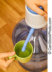 Woman hands pouring water in green mug from bottle with water pump.