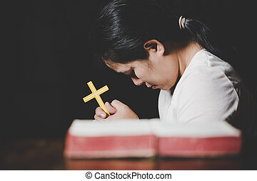 Woman hands praying with a cross and bible in a dark over wooden table