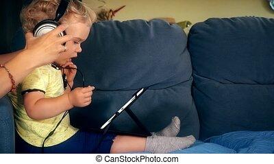 Woman hands put big headphones on daughter with tablet computer head.