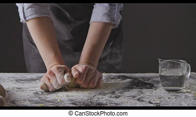 Woman hands put flour on a table and knead homemade gough ...