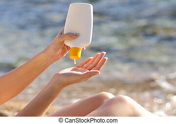 Woman hands putting sunscreen from a bottle on the beach...