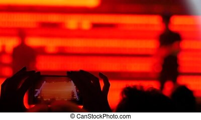 Unrecognizable woman hands silhouette taking photo or recording video of live music concert with smartphone in front of stage of nightclub. Photography, entertainment, technology concept