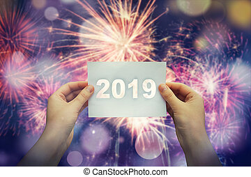 Woman hands rised up to the sky holding a white paper sheet with 2019 text in the middle. New year fireworks celebration, holiday concept.