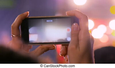 Woman hands silhouette recording video of live music concert with smartphone